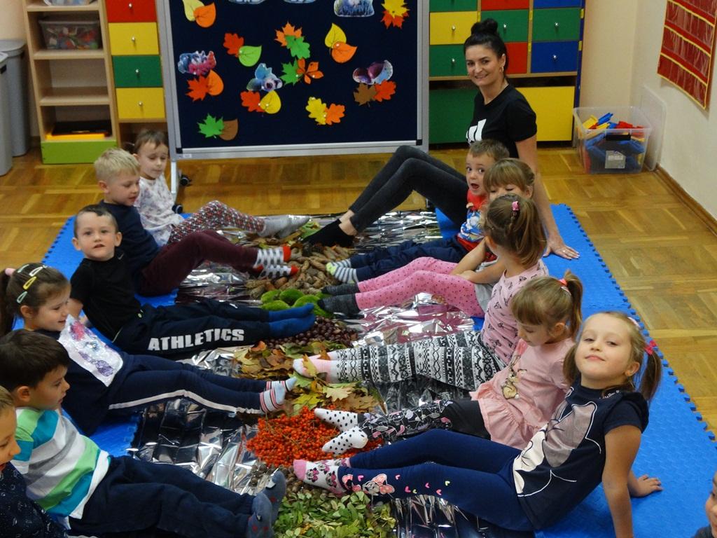 Dzieci i nauczycielka dotykające stopami swoich zbiorów