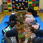 Dzieci dotykające rękoma materiałów z lasu