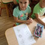 Dziewczynka koloruje jesienne obrazki