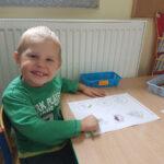 Chłopiec koloruje jesienne obrazki