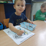 Chłopiec koloruje rysunek