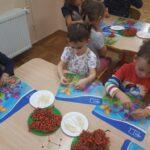 Dzieci tworzą figury z jarzębiny