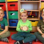 Dzieci oglądają w przedszkolu kawałki drzew
