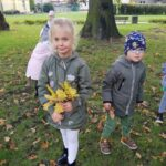 Dzieci bawią się na spacerze z liśćmi