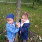 Dzieci bawią sie na dworze z liśćmi