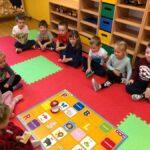 Dzieci siedzą na macie podczas zabaw