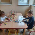 chłopiec i dziewczynka układają puzzle