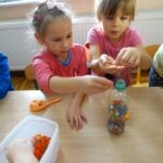 Dzieci wsypują kulki do butelki