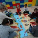 nauczyciel i dzieci bawią się na dywanie