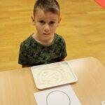 Chłopiec rusuje wzory na mące