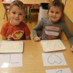 Chłopiec z dziewczynką rysują wzory na mące