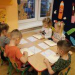 Dzieci rysują wzory na mące
