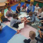Dzieci z grupy Tulipanków rozpakowują prezent od Mikołaja