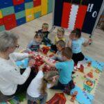 Dzieci z grupy krasnoludków rozpakowują prezent