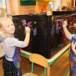 Dziewczynka maluje farbami na czarnej folii