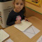 Dziewczynka rysuje wzory na mące
