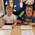 Dziewczynka z chłopcem rysują wzory na mące