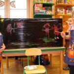 Dziewczynki malują farbami na czarnej folii
