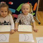 Dziewczynki rysują wzory na mące