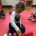 dziewczynka gra w kubki
