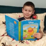Chłopiec czytający bajkę Kubusia Puchatka