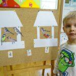 Chłopiec przy tablicy wykonuje zadanie matematyczne z ptakami w karmnikach