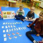 Chłopiec układa ptaki na dywanie zgodnie z podaną cyfrą