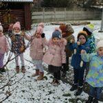 Dzieci na placu przedszkola trzymają przygotowaną karmę, która za chwilę powieszą na krzewie.