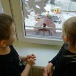 Dzieci obserwują przy oknie karmnik, w oczekiwaniu na przylot ptaków