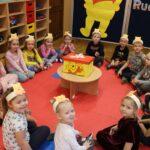 Dzieci siedzące w kółeczko oraz perezt na stoliku