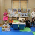 Dzieci w sali przedszkolnej z tablicami i planszami edukacyjnymi nt. ptaków