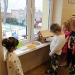 Dzieci wsypują ziarna do karmnika