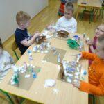 Dzieci wykonuja przestrzenne prace plastyczne- karmnik z ptakami