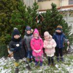 Dzieci z grupy Mrówek przed karmnikiem na placu przedszkola