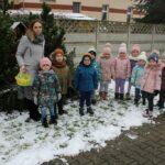 Dzieci z nauczycielką przed karmnikiem na placu przedszkola