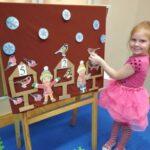 Dziewczynka przyczepia na tablicy ptaki do karmnika