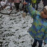 Dziewczynka wiesza karmę na drzewie