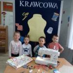 Dzieci stoją przy tablicy z napisem Krawcowa