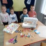 Dzieci stoją przy stoliku z przyborami krawcowej