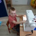 Chłopiec siedzi przy maszynie do szycia
