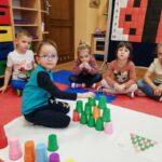 Chłopiec układa wieżę z kolorowych kubeczków