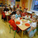 DZieci z grupy Biedronek siedziące przy stolikach z poczęstunkiem