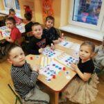 Dzieci siedzące przy stolikach przyklejają obrazki według podanego kodu (1)