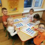 Dzieci siedzące przy stolikach przyklejają obrazki według podanego kodu (2)