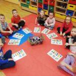 Dzieci układają klocki na kartach zgodnie z podanym kodem