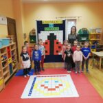 Dzieci z nauczycielką stoja przy tablicy z zakodowaną biedronką