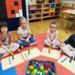 Dzieci z ułożonymi wieżami z klocków zgodnie z podanym kodem (1)