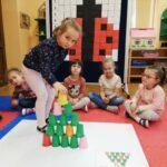 Dziewczynka układa wieżę z kolorowych kubeczków