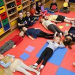 DZieci leżą na dywanie tworząc figury geometryczne