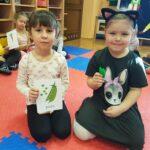 Dwie dziewczynki są na zdjęciu. Jedna trzyma planszę z nazwą groszku po angielsku, a druga trzyma groszek w ręku